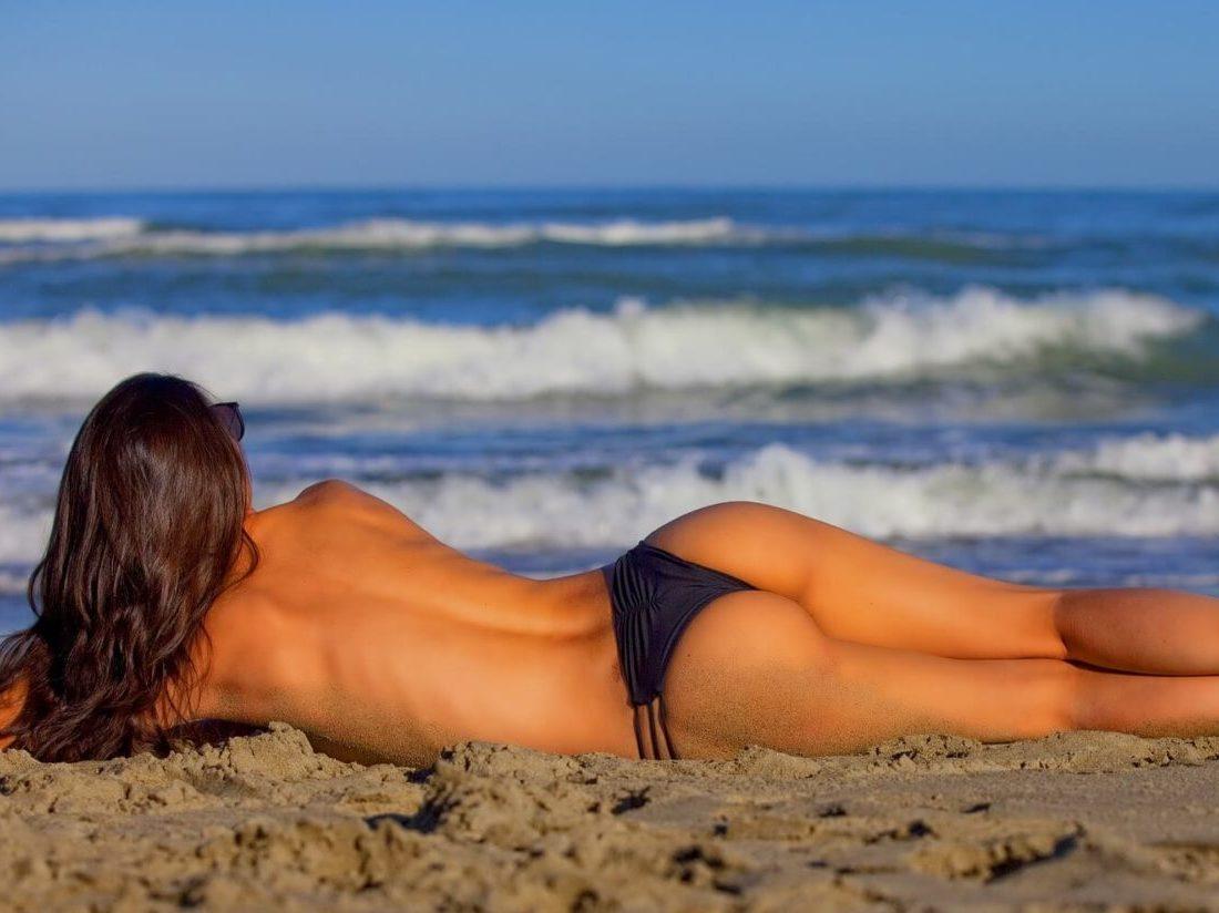 砂浜に横たわるスタイルの良い女性