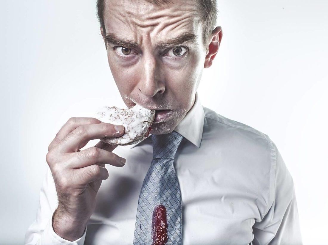 パンを食べるスーツ姿の男性