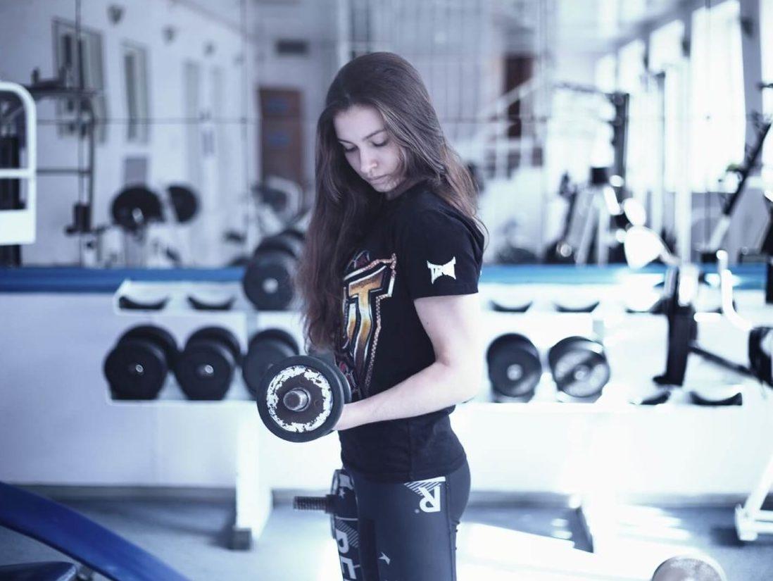 フィットネスクラブのダンベルでトレーニングする女性