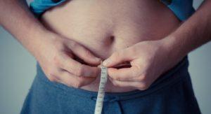 お腹周りを測る太った男性