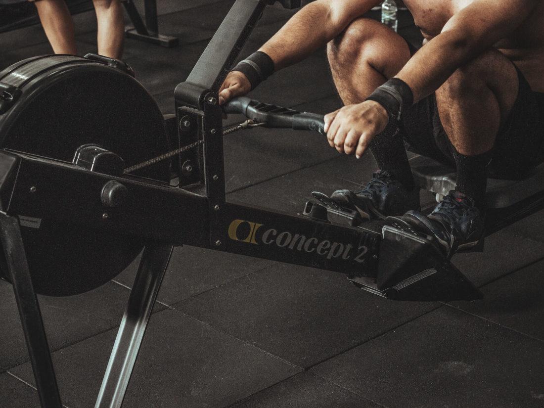 ローイングマシンでトレーニングする男性